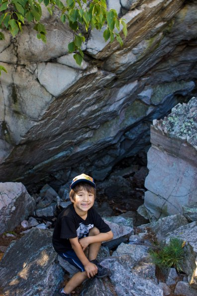 A young boy smiles while sitting in front of the entrance of a rock slide cave - Hiking the Crack in Killarney with Kids
