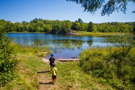 Two young boys walk towards a small lake in Ontario - Hiking the Crack in Killarney with Kids