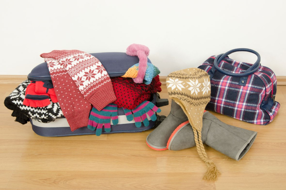 Luggage overflowing with winter clothes on a wood floor - plan international family vacations