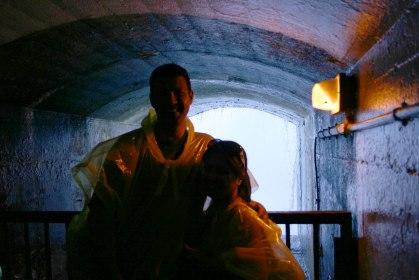 A young couple smiles in a tunnel beneath Niagara Falls - Exploring Niagara Falls