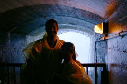 A young couple smiles in a tunnel beneath Niagara Falls - Exploring Niagara Falls