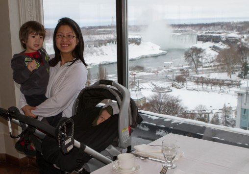 Mother with children at the dining area of the Sheraton on the Falls hotel with Niagara Falls in the background.