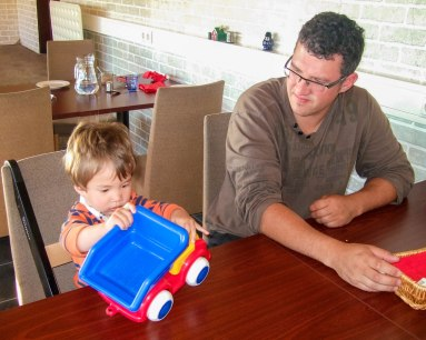 A father watches his toddler son play with a toy truck at a restaurant