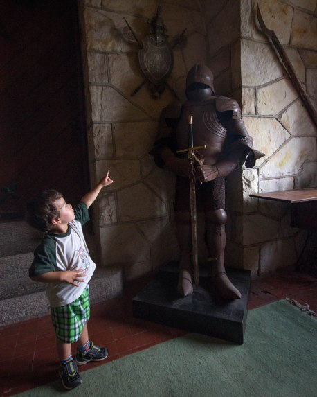 Boy excitedly points at a knight's armour in Singer Castle, one of the castles in the Thousand Islands National Park.