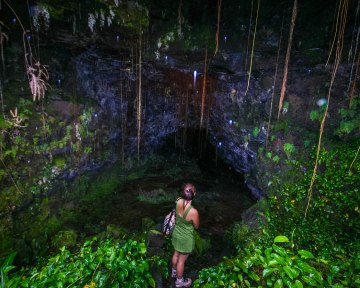 Woman looking at the entrance of a giant lava tube in Big Island Hawaii.