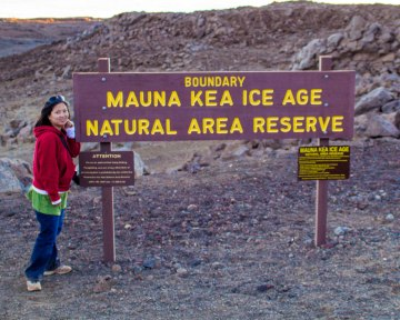 Woman standing beside the Mauna Kea Ice Age Natural Area Reserve sign