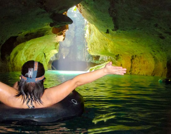 A woman in a tube floats towards a beautiful cave entrance with her arms outstretched