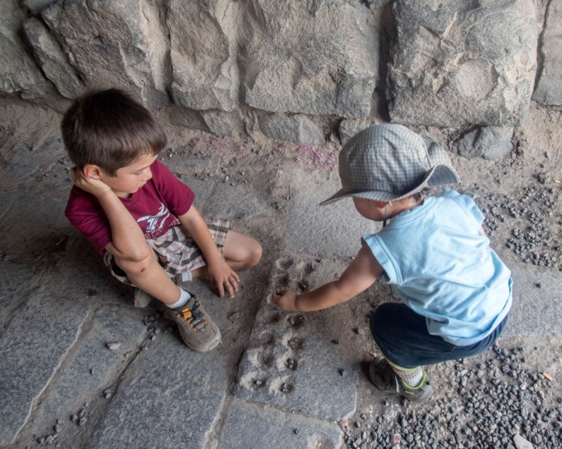 Two young boys play a game of stone etched into the floor of one of the castles in Jordan