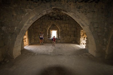 A woman and a young boy explore a room in a desert castle that once housed the famous T.E. Lawrence