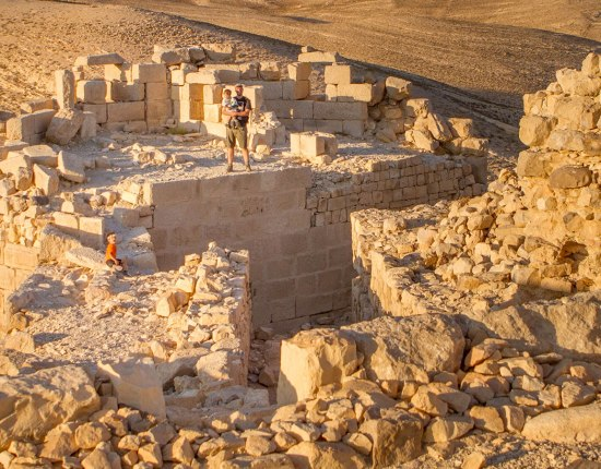 A father and two young boys walk along the roof of a castle in Jordan