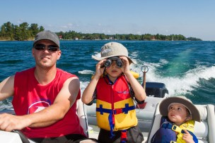 A father and two young boys in a motor boat on Thousand Islands National Park the older boy is looking through binoculars at the camera