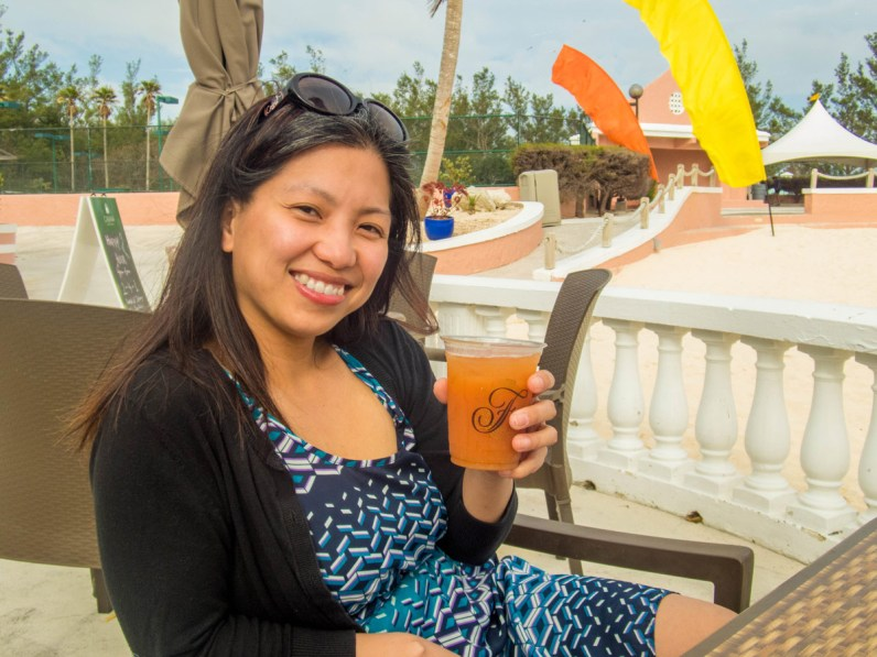 A young asian woman sips a drink at a beach bar in Horseshoe Bay Beach, Bermuda