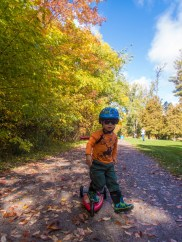 A young boy riding a scooter while wearing a helmet and sunglasses at Jackson Park in Peterborough, Ontario