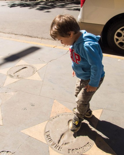 Little boy looking at a footprint outside La Bombonera stadium in La Boca district of Buenos Aires.