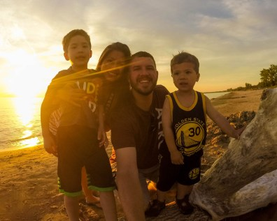 A family poses for a photo at sunset in Sauble Beach Ontario