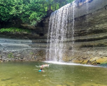 A father and young boy swim under a waterfall on Manitoulin Island