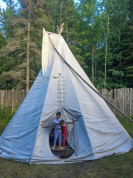 two boys wearing pajamas wake in a teepee at Great Circle Trail on Manitoulin Island