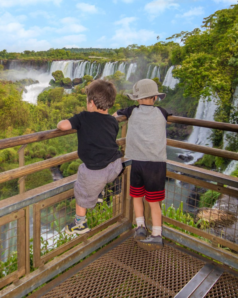 Two young boys look out over Iguazu Falls Argentina. The younger boys is trying to climb the fence. It's worth visiting Iguazu Falls Argentina with kids.