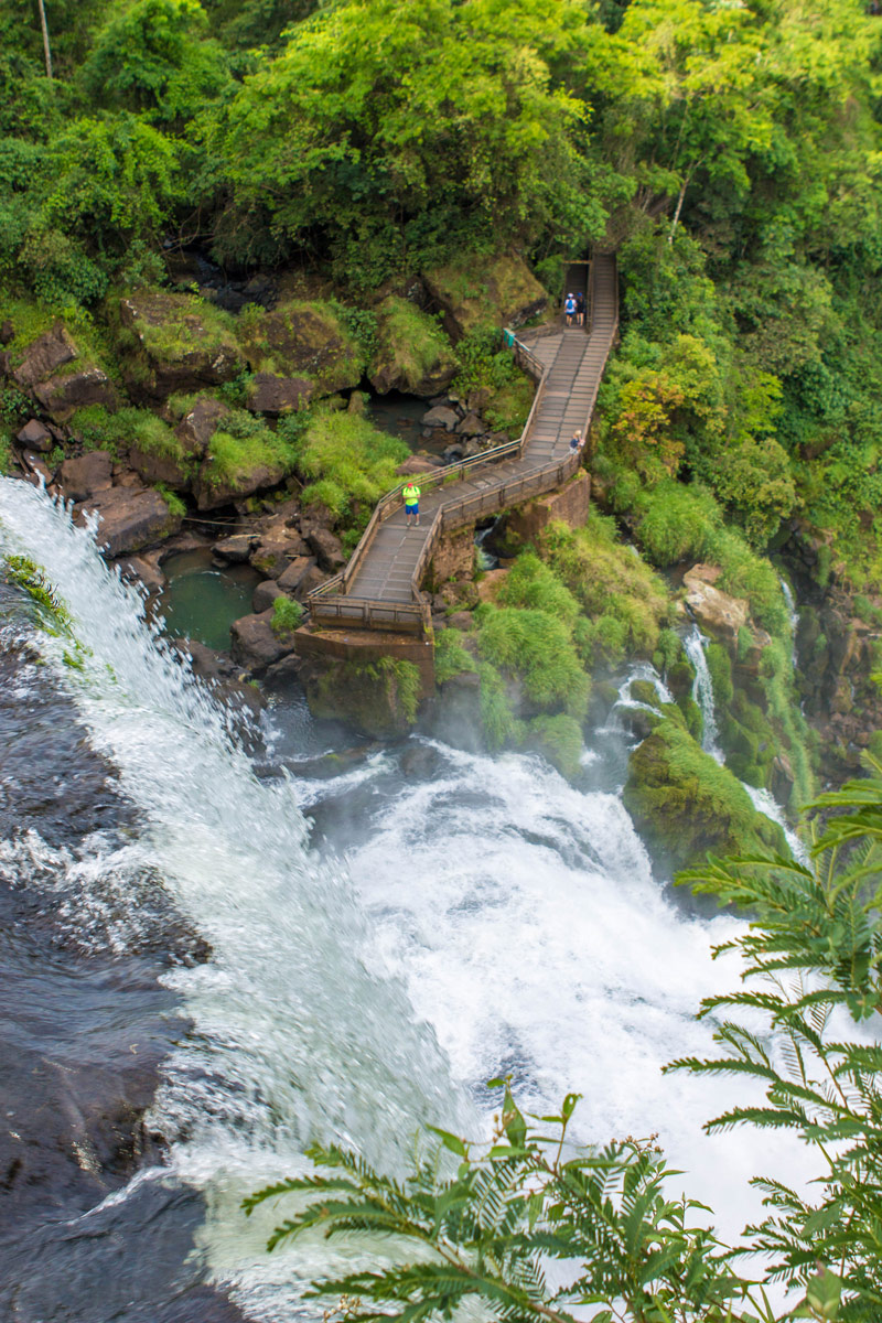 Looking over the edge of a coarsing waterfall. A small catwalk is beneath it with visitors watching the watefall
