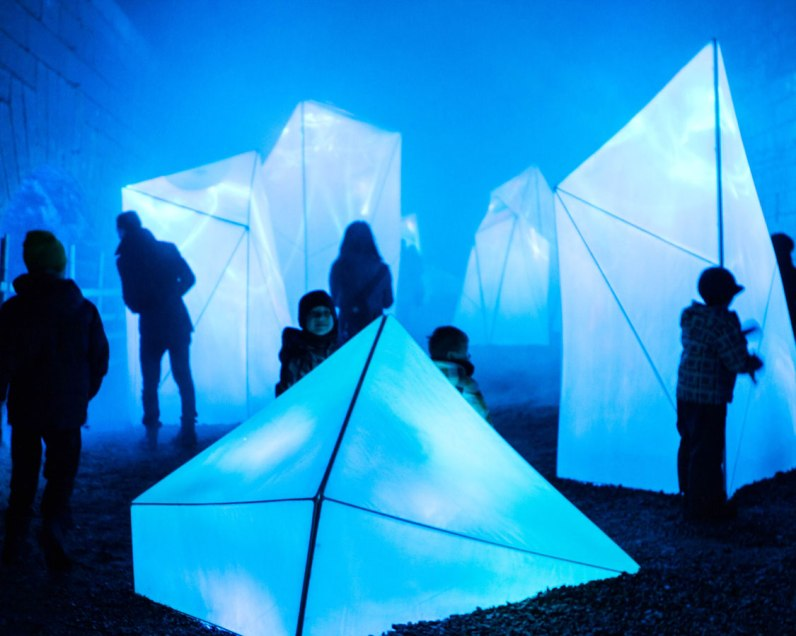 People looking at an Iceberg art installation a great place for exploring when visiting Lumina Borealis with kids.