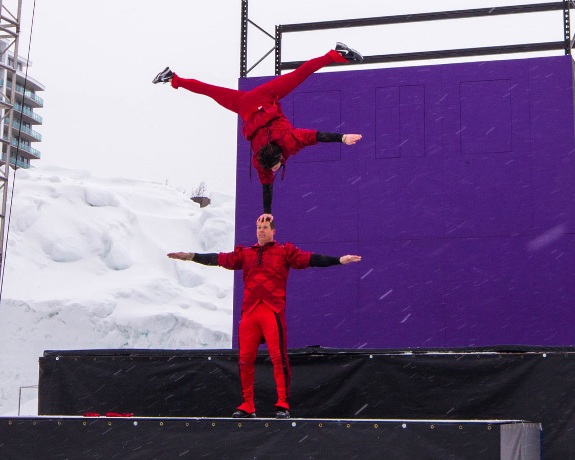An acrobat balances himself on the head of another acrobat.