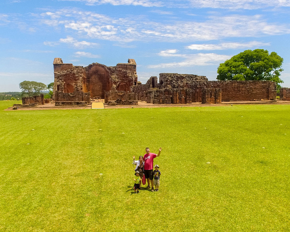 A young family waves to a drone taking the photo in the Jesuit ruins in Paraguay