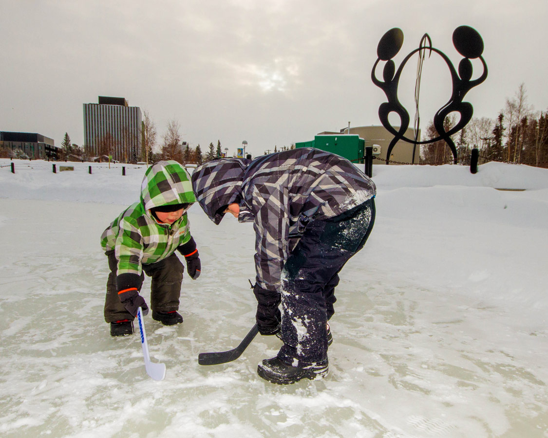 Boys playing hocked on an outdoor rink in Yellowknife.