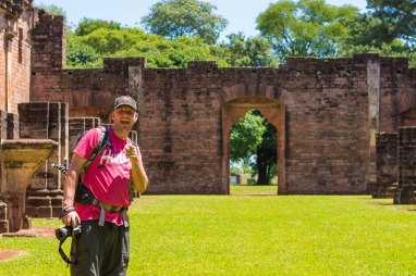 Man smiles and points at a camera in the ruins of Jesuit Missions in Paraguay