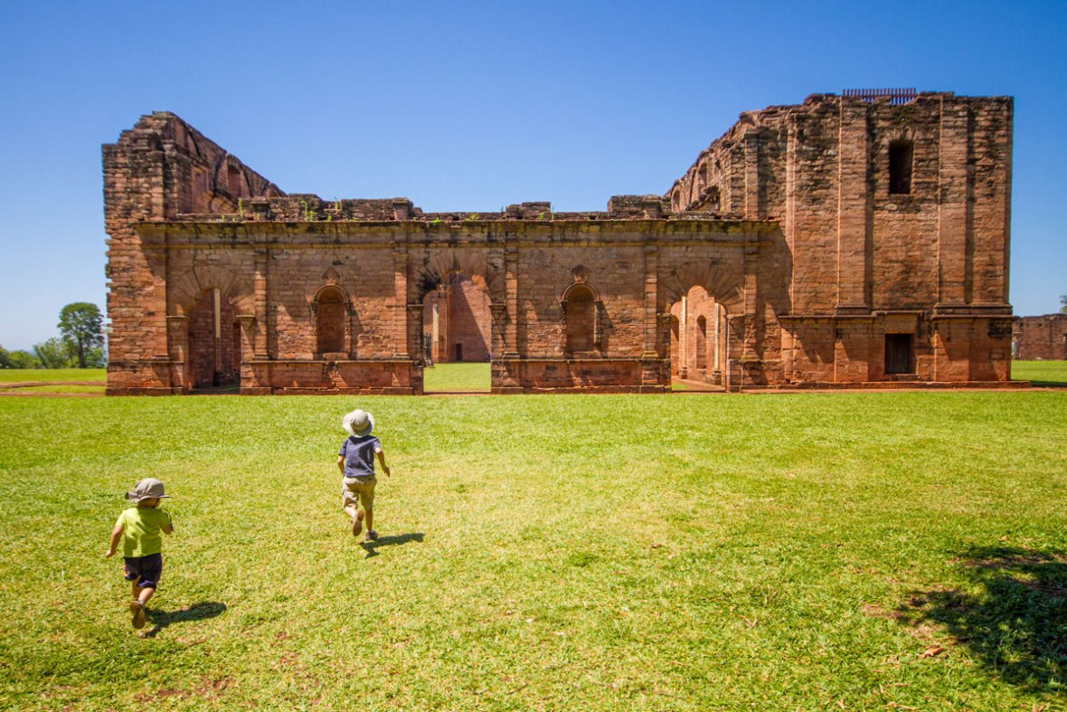 two young boys run across a field towards the ruins of a Jesuit mission in Paraguay