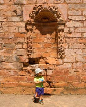 A young boy snacks under an arch in the ruins of the Jesuit church in la Santisima Trinidad de la Parana in Paraguay