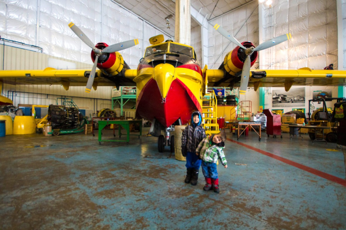 Two boys pose in front of a water bomber in the Buffalo Airways hanger in Yellowknife.