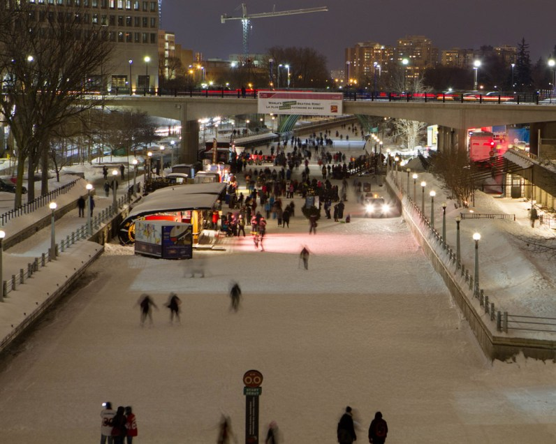 View of Rideau Canal Skateway filled with ice skaters during the Winterlude festival at night.