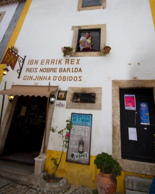A father and baby pose on the second floor window of the Bar Ibn Errik Rex in Portugal