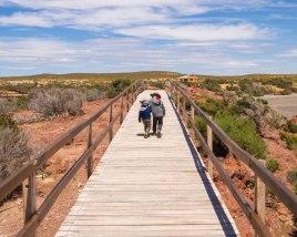 Two boys walk arm in arm along a boardwalk in Punta Tombo Argentina