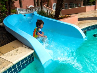 Boy going down a waterslide into the kiddie pool at the Fairmont Southampton Hotel Bermuda.