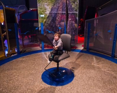 Small boy flaps a makeshift wing at the Ontario Science Centre Bio Mechanics Exhibit