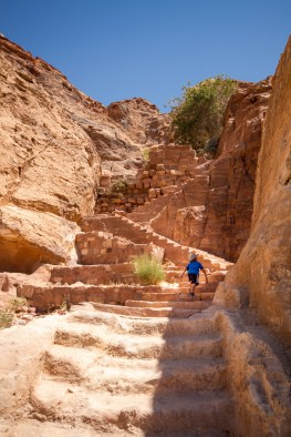 A young boy climbs up stone steps among the cliffs of Petra Jordan on the way to the high place of sacrifice