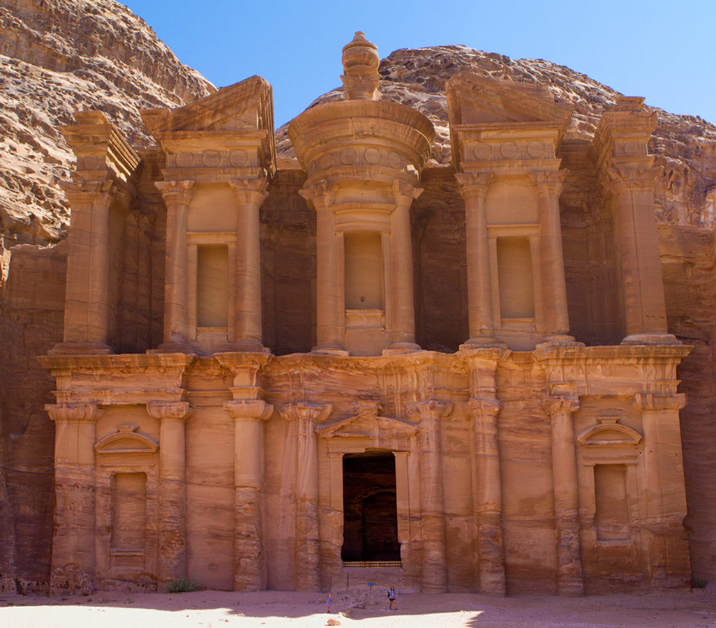Petra with kids A woman and child are dwarfed by the Monastery in Petra Jordan