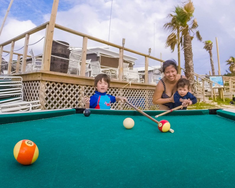 Woman and two boys playing outdoor billiards in Tobacco Bay, St George Bermuda.