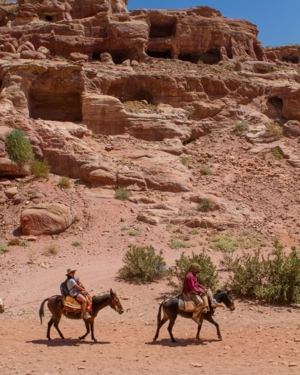 A Bedhouin guide and a woman on horseback ride past cave houses in Petra Jordan