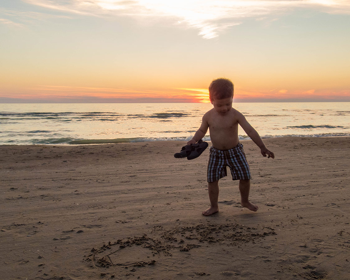 Boy tries to write in the sand during sunset at Sauble Beach.