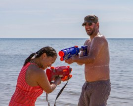 Man and woman having a water gun fight at Sauble Beach, Ontario.