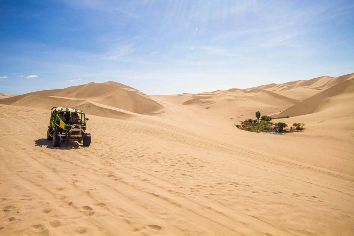 A dune buggy drives through the desert near an oasis as it's occupants prepare to go sandboarding in Peru wtih kids near Huacachina