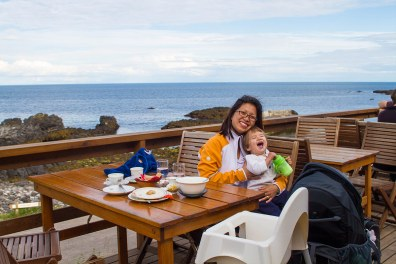 A mother and son laugh together on the patio of an Icelandic cafe overlooking the Atlantic ocean in Hellnar