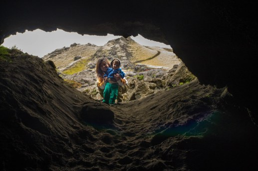 A woman and a toddler peer into a lava tubes in Laki Iceland
