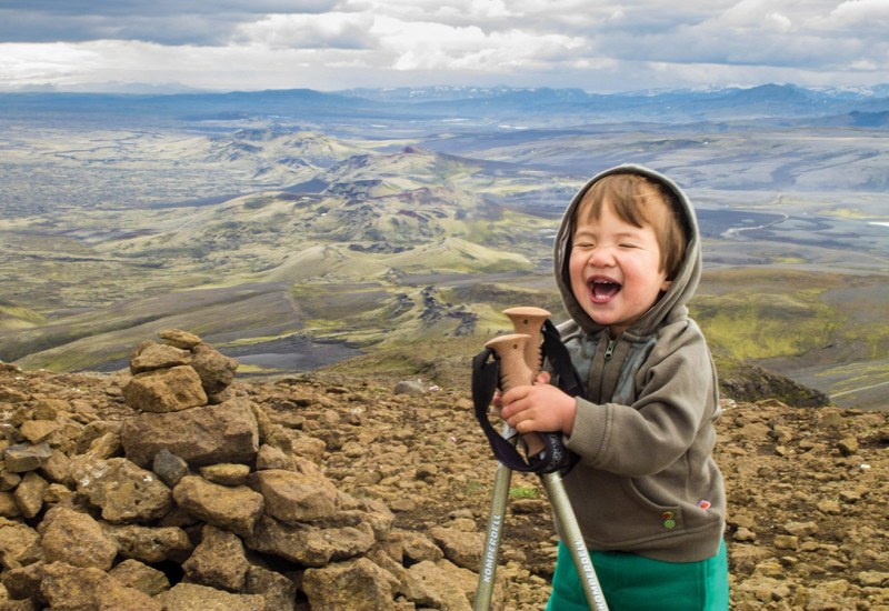 A young boy laughs on the top of a mountain in Laki Iceland as he explores family friendly hikes in Iceland