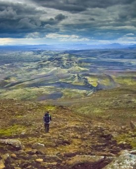A man carrying his infant child hike along the Lakigigar Crater Row in Iceland