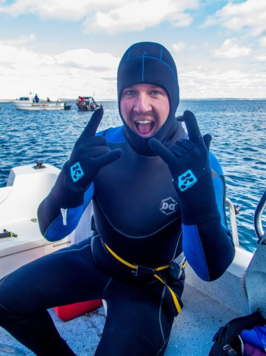 A smiling man in a wet suit gives a rock star symbol as he prepares to go SCUBA diving with sea lions in Punta Loma Argentina