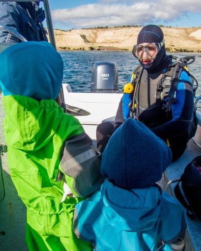 A man in SCUBA gear sitting on the back of a dive boat talks to to young boys before going SCUBA diving with sea lions in Punta Loma Argentina