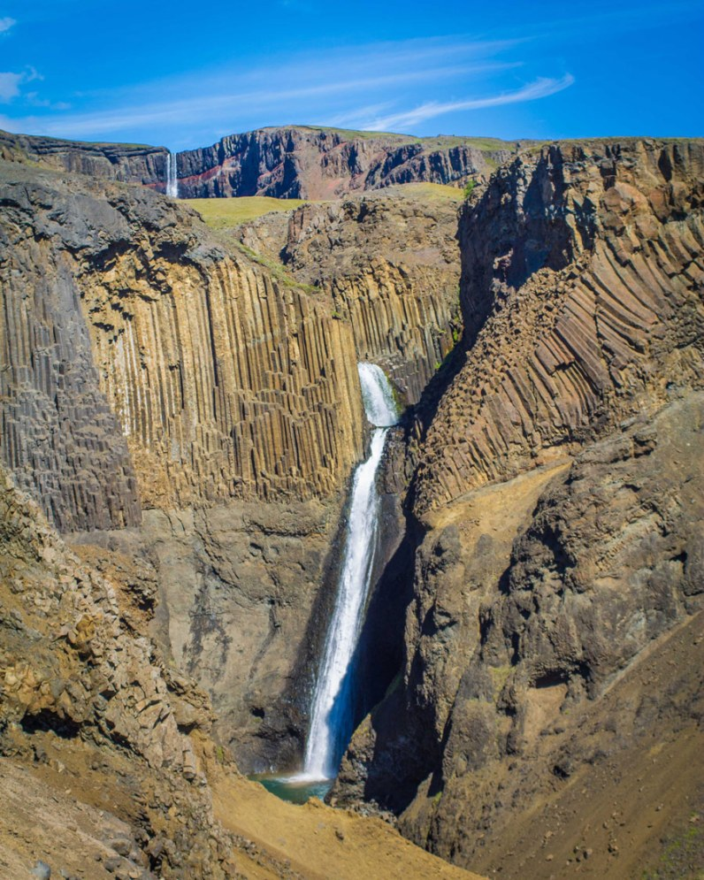 A dramatic and tall, narrow waterfall pours from the rocks in Iceland